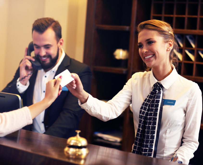 Friendly corporate lodging checking at hotel front desk / Man and woman work at a hotel front desk checking in guests