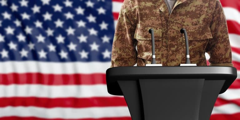 A military person standing at a lectern in front of an American flag